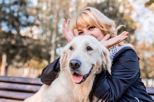 Pet care concept. Young smiling woman showing horns of her retriever dog in the park