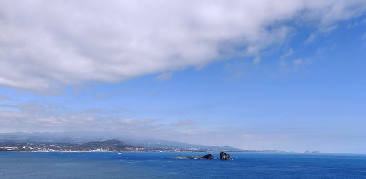 Bright blue never-ending sea with white clouds in the blue sky in Jeju Island, South Korea