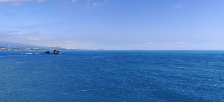 Wide angle shot of the brightest blue empty ocean and sky in Jeju Island, South Korea