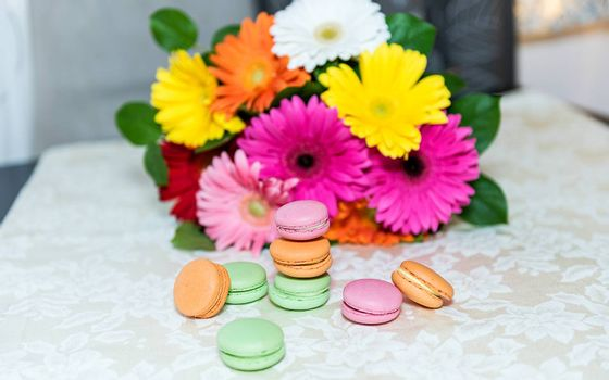 Colorful mix of macarons with a background of gerbers for decoration