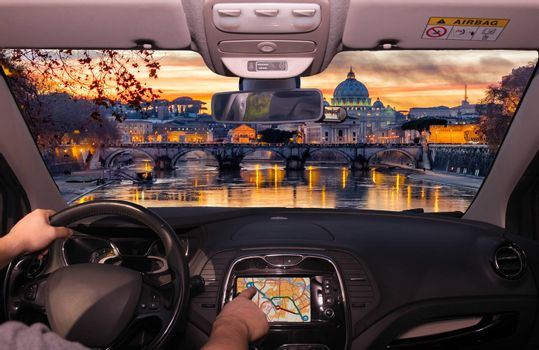 Driving a car while using the touch screen of a GPS navigation system towards Saint Peter's Church during a wonderful sunset in Rome, Italy