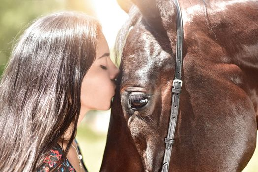 Horse and girl share an emotional moment in close up shot as they appear to kiss.