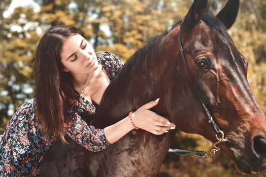 Pretty Hispanic brunette giving her horse a hug while riding him in the forest