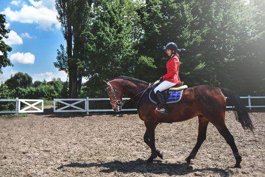 Young pretty jockey girl preparing horse for ride. love horses