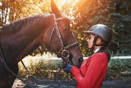 A young girl talking and kissing her horse. She loves the animals and joyfully spends her time in their environment.