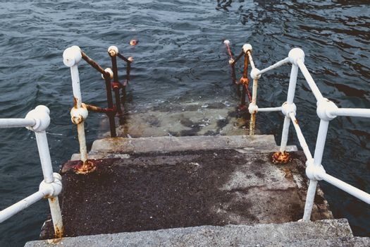 concrete staircase with white metal barriers sinking into the water - concept