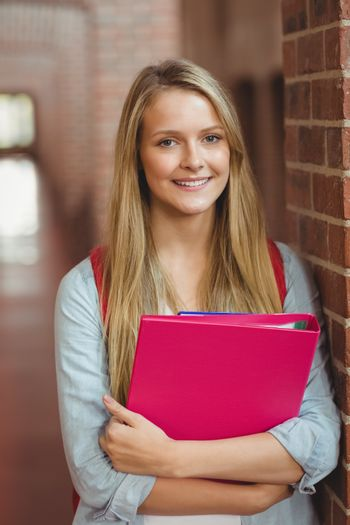 Smiling student with binder posing