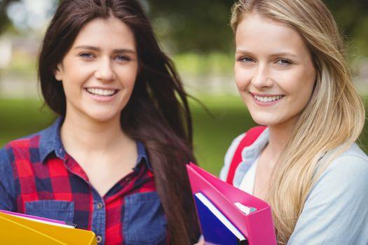 Smiling students holding binder