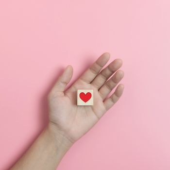 Hands holding Wood cube with  red heart on pink background. Valentines day, Love concepts.