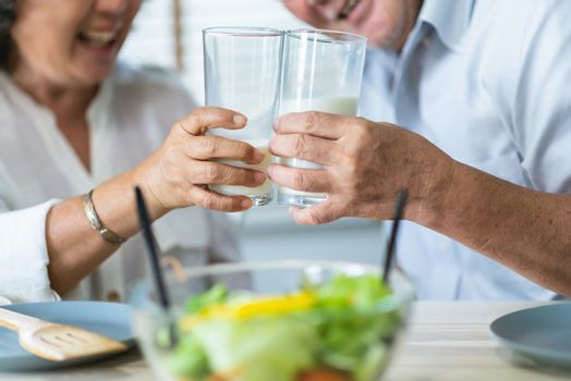 Healthy asian Elderly couple enjoying drinking fresh milk from glass. Happy Smiling Senior man and woman having fun with breakfast in the morning.
