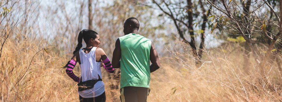 Happy African couple jogging in a autumn nature. Banner, Panoramic view. Healthy lifestyle and sport concepts