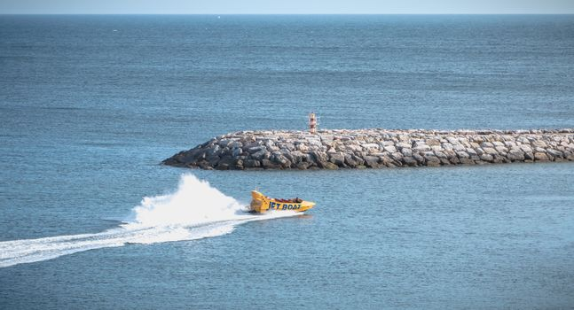 Albufeira, Portugal - May 3, 2018: Jetboat for tourists entering the harbor at full speed on a spring day