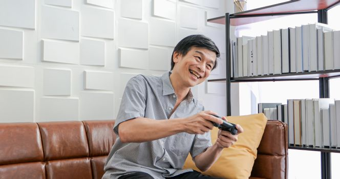 Senior Asian man using tablet and virtual reality simulator playing games in living room and feeling happy . Lifestyle Senior family at home concept.