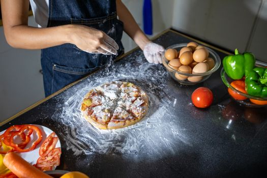 Asian women preparing a pizza, knead the dough and puts ingredients on kitchen table