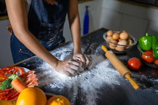 Asian women preparing a pizza, knead the dough and puts ingredie