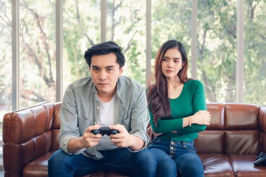 Portrait of Woman Feeling Offended With Her Boyfriend When He Playing Video Games While Sitting on The Couch in Living Room. Couple Love Relationship and Lifestyles Concept.