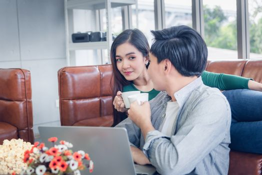 Couple Love Having Relaxation Discussing While Drinking a Coffee in Their Home, Attractive Asian Couple Happiness in Romantic Moments at Living Room. Relaxing and Lifestyles Concept