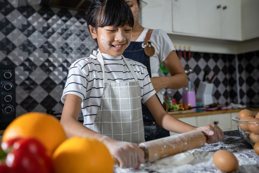 Asian families are cooking  and parents are teaching their daughters to cook in the kitchen at home.  Family activities on holidays and Happy in recreation concept