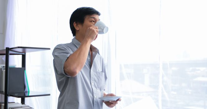 Senior Asian man drinking coffee on relaxing time