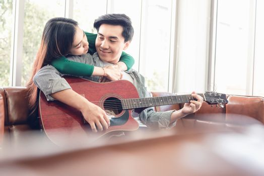 Young Couple Love Relaxing on Sofa in Living Room While Playing Guitar and Enjoyed Sing a Song at Home Together. Romantic Asian Couple Relaxation Enjoying Leisure Activity at Their Home. Stay at Home