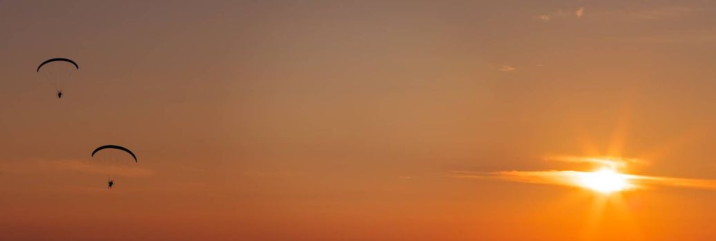 Paragliders flying with a paramotors during beautiful sunset