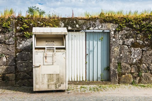 Vila Cha near Esposende, Portugal - May 9, 2018: Public containers for retrieving toy and clothes (Roupa Brinquedos) in front of a stone wall in the city center on a spring day