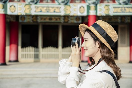 happy female traveler photographing temples at  Asia