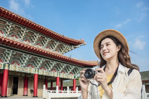 happy asian female traveler photographing temples at  Asia