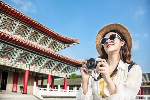 asian female traveler photographing temples at  Asia