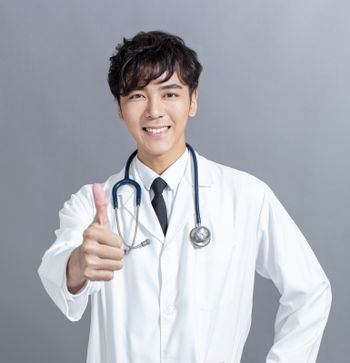 friendly asian doctor  giving thumbs up