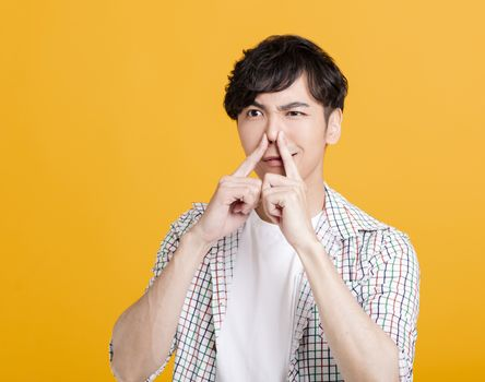young man hand holding his nose