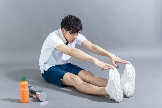 young man runner doing stretching exercise