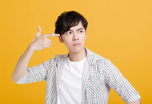 Young man  pointing his fingers at  head