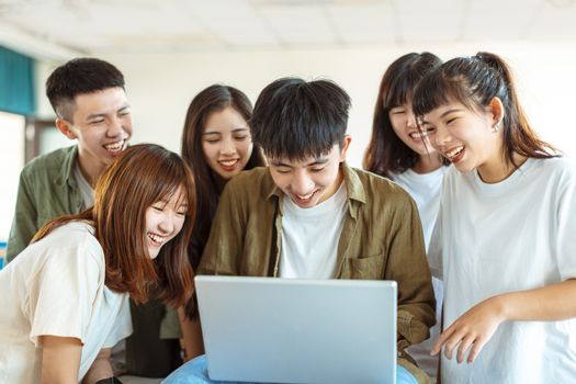 excited college students looking at laptop  in classroom