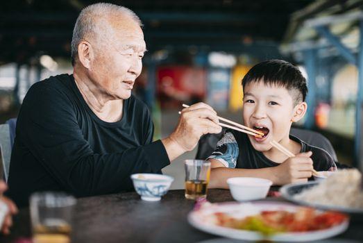 Granfather feeding her grandson in restaurant