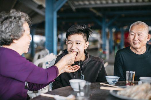 Grandmother feeding her teenager grandson in restaurant