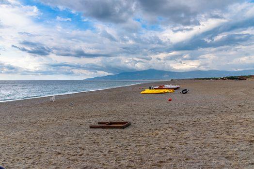 Pedalos and kayaks on a gravel beach at the Tyrrhenian Sea in Calabria, Italy