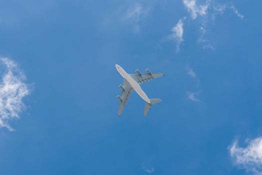 Bottom view of passenger airplane against clear blue sky