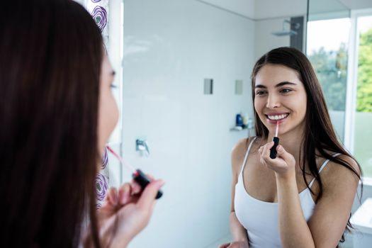 Brunette applying lip gloss