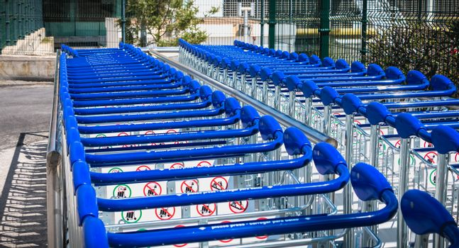 Faro, Portugal - May 3, 2018: carry cart outside Faro international airport available to travelers to move their luggage on a spring day