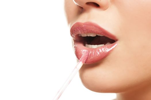 beautiful woman apply a lip gloss on her lips