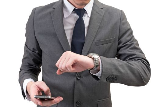 Businessman checking time on his wrist watch and holding mobilephone isolated on white background