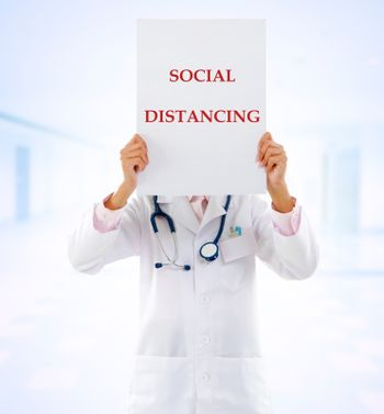 Medical doctor holding a card with social distancing on it.