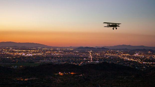 Bi-plane over Phoenix, AR at sunset