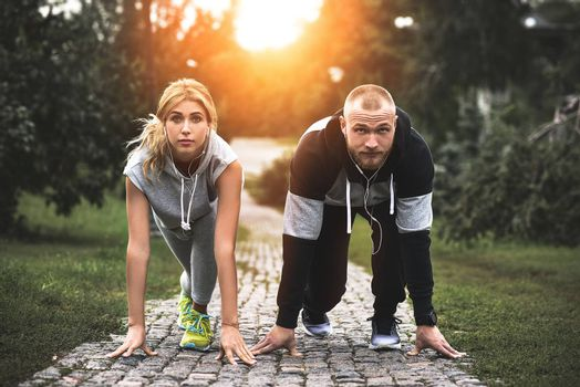 Urban sports - couple jogging for fitness in the city with beautiful nature.