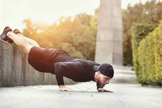 Young bearded sportsman makes workout in a park, doing a series of push ups outdoor.