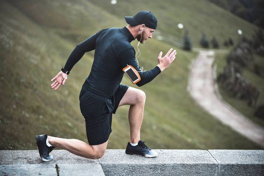 Young caucasian male jogger with fitness tracker attached to arm do warming up before jogging.