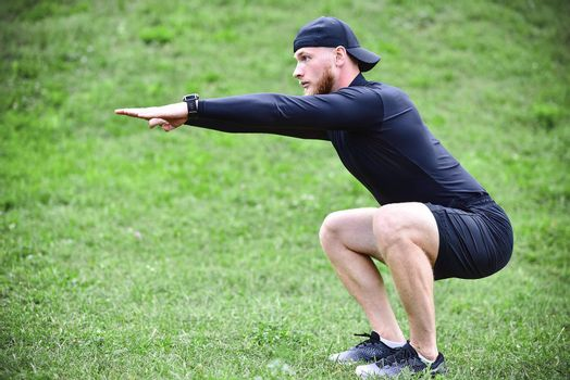 Full length of young concentrated sportsman doing squats outdoors.