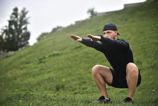 Young caucasian man performing squats before jogging on footpath in park.