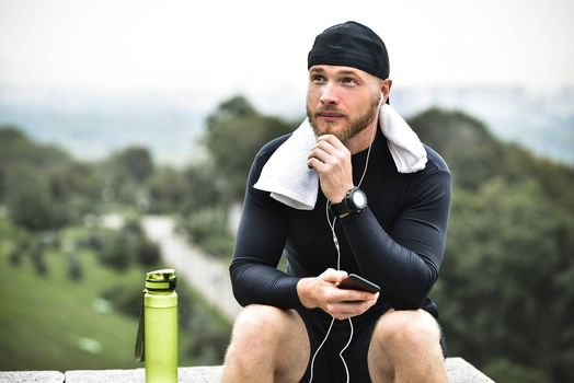 Muscular bearded athlete with towel checking burned calories on smartphone after good workout session on city park.